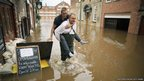 A man carries another through floodwater as the swell of the River Ouse flows through the city of York, England.