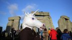 A person wearing a unicorn costume at Stonehenge