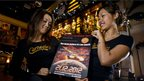 bar staff in Hong Kong hold a poster advertising an 'End of the World' party