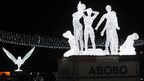 A view on December 14, 2012, in Abidjan, of an illuminated installation made of light sculptures representing a dove and women who were killed at a roundabout in the Abobo district of Abidjan during post-electoral violence in 2010-2011.
