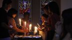 Worshippers light candles and dedicate prayers at the Rosebank Catholic Church in Johannesburg on 16 December.