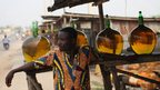 "A vendor sells fuel, known locally as ""kpayo"", at the side of the road on 6 January 2012 in Cotonou, Benin"