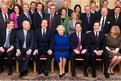 Britain's Queen Elizabeth II sits flanked by British Prime Minister David Cameron and Deputy Prime Minister Nick Clegg (R) as members of the Cabinet pose for a family picture at No 10 Downing Street