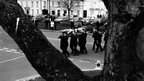 Police funeral viewed through the boughs of a tree.