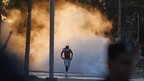A man who tried to loot a supermarket runs away from tear gas in San Fernando, on the outskirts of Buenos Aires December 21