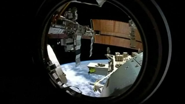 View of the ISS and Earth from one of the space station's portholes