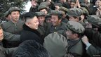 North Korean leader Kim Jong-Un (centre) celebrates with scientists and technicians at the General Satellite Control and Command Center after the launch of the Unha-3 (Milky Way 3) rocket