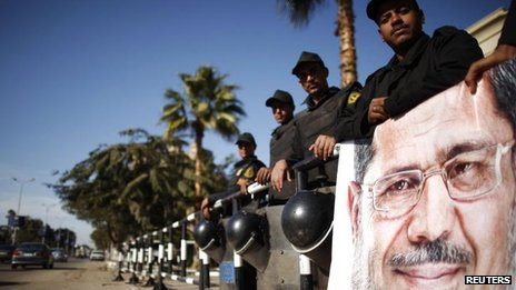 Police stand guard near a banner outside the constitutional court put up by supporters of President Mohamed Morsi, 23 Dec