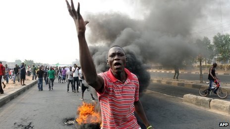 A protester in  front of a burning tyre in Lagos, Nigeria (January 2012)