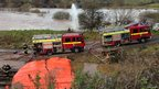 Fire engines pumping flood water and flooded train tracks in Exeter, Devon