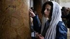 A Catholic pilgrim touches a column inside the Church of the Nativity. Photo: 24 December 2012