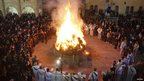 Iraqi Christians gather around a fire as they celebrate Christmas in a church in Hamdaniya town, east of Mosul