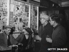 A group of men in a pub look over a  war-time cartoons in a pub lounge