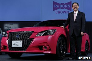 Toyota president Akio Toyoda poses next to the company's remodelled Crown Athlete car