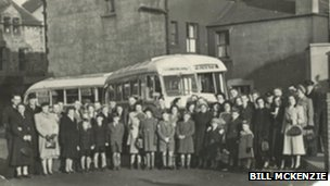 People standing near a bus in the 1950s