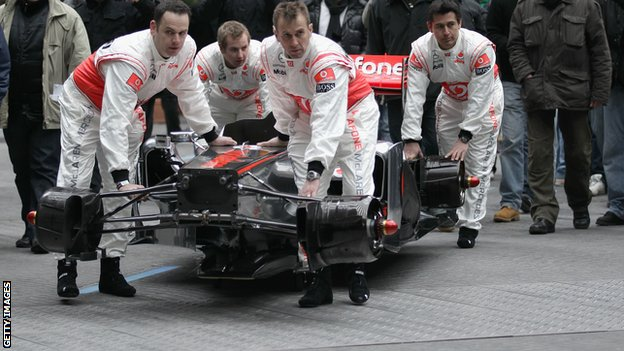 Mclaren mechanics carry the chassis of the  McLaren Mercedes MP4-26
