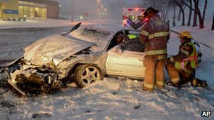 Emergency workers assist the driver of a car which has crashed on a snow-covered street in Columbus, Indiana