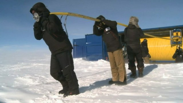 Scientists carrying equipment in Antarctica