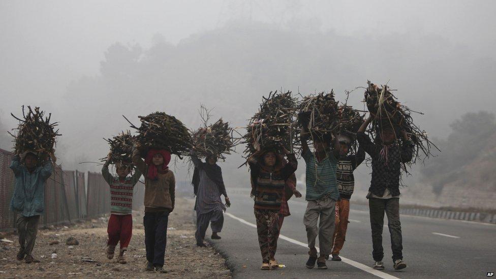 Indian children carrying firewood through fog, Jamuu, India - 27 December 2012