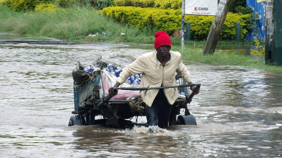 A man pulling a cart through floodwaters in Nairobi, Kenya - 27 December 2012