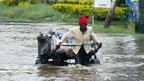 A man pulling a cart through floodwaters in Nairobi, Kenya - 27 December 2012