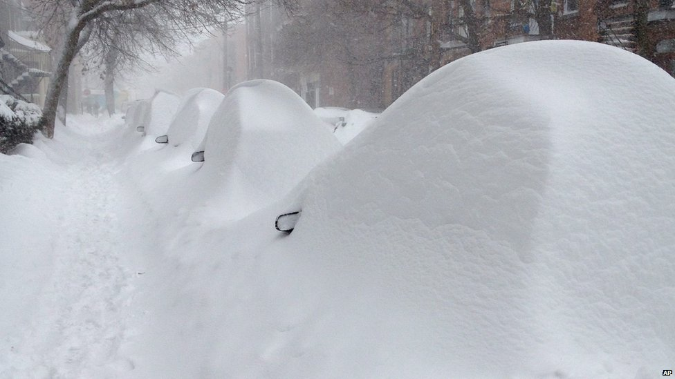 Parked cars hide under mounds of snow on Darling Street in Montreal 27 December 2012