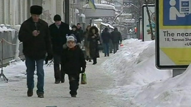 People walk on snow covered street in Ukraine