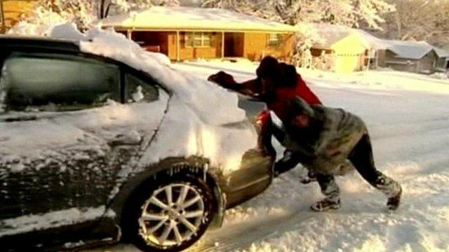 People pushing car in snow