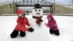 Desiree Smith, 13, left, and Madison Garza, 7, both from San Diego, build a snowman at the Millenium Circle in Wilkes-Barre, Pennslyvania, 27 December 2012