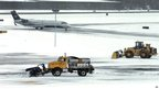 Snow is cleared on a runway as a plane taxis into Manchester-Boston Regional Airport in Manchester, New Hampshire 27 December 2012