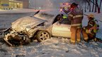 Rescuers try to move a driver injured in a wreck on a snow-covered street in Columbus, Indiana 6 December 2012