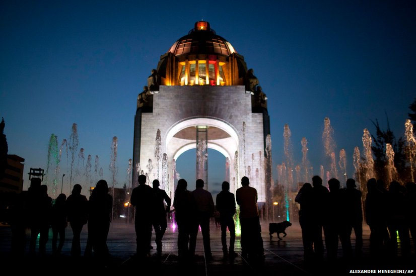 Pedestrians stand in front of the Arch of the Revolution monument in Mexico City
