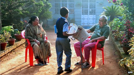 A delivery boy gives a newspaper to a 66-year-old Anglo-Indian resident of McCluskieganj, eastern India, as the man sits in his garden with his Indian wife, in October 2011