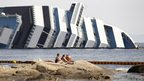 People relax in front of the wreckage of capsized cruise liner Costa Concordia near the harbour of Giglio Porto