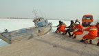 Fire fighters and soldiers pull an icebound ship in the frozen Bohai Bay of Bohai Sea in Jinzhou, China