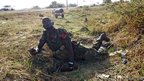 An SPLA soldier looks at warplanes as he lies on the ground to take cover beside a road during an air strike by the Sudanese air force in Rubkona