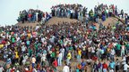 People gather on a hill in Marikana after attending a memorial service for those killed at Lonmin's Marikana mine.