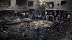 People gather around a crater caused by an Israeli air strike in Gaza City