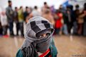 A boy walks past a queue of Syrian refugees waiting to receive aid from Turkish humanitarian agencies at Bab al-Salam refugee camp in Syria