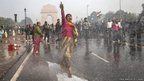 A protester chants slogans as she braces herself against the spray fired from Police water canons