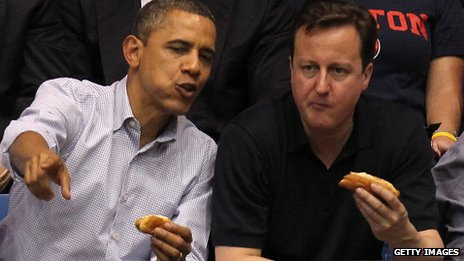 US President Barack Obama and British Prime Minister David Cameron eat hot dogs at a basketball match