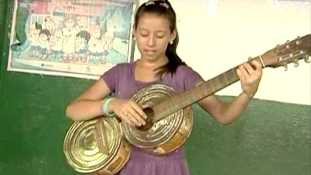 Girl plays guitar made of old cans