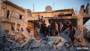Men search for survivors after an air strike by a fighter jet loyal to Syrian President Bashar el-Assad in Azaz city, North Aleppo, 29 December 2012