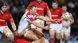 Ulster skipper Roger Wilson gets his pass away despite Munster pressure