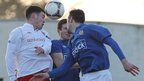 Linfield midfielder Brian McCaul gets his head to the ball despite the close attention of two Glenavon players at Mourneview Park