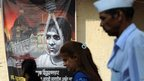 Pedestrians in Mumbai walk past a poster depicting Qasab's hanging outside a railway station in Mumbai on 26 November 2012