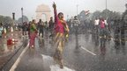A protestors chants slogans as she braces herself against the spray fired from Police water canons during a protest against the Indian governments reaction to recent rape incidents in India, in front of India Gate on December 23, 2012 in New Delhi