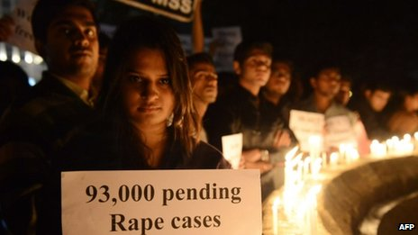 Protesters hold candles and posters during a rally in India on 30 December 2012
