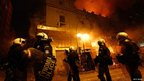 Greek riot police watch a blaze in Athens during rioting, 12 February