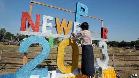 A Burmese worker puts up a sign to bring in the new year ahead of the country's first public new year countdown